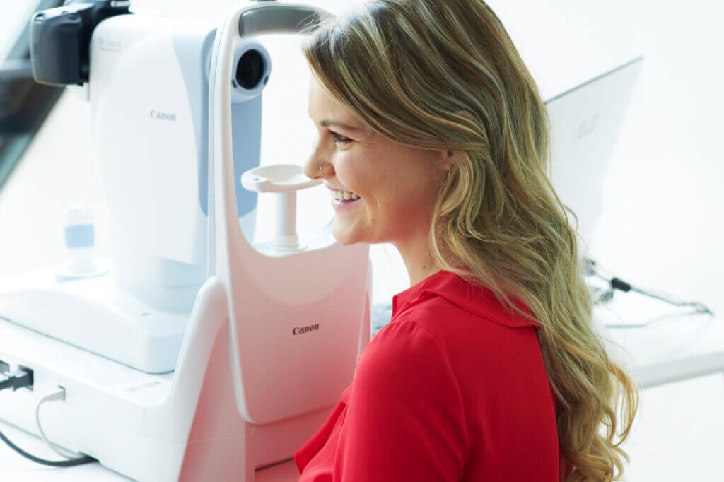 Eine Patientin der Augenarztpraxis Roman Eyes lacht entspannt in einer Behandlungssituation