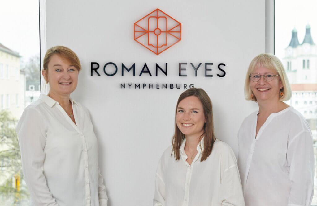 Das Team der Augenarztpraxis Roman Eyes Nymphenburg vor dem Logo der Privatpraxis, geführt von Dr. Doris Ruskovic, Fachärztin für Augenheilkunde